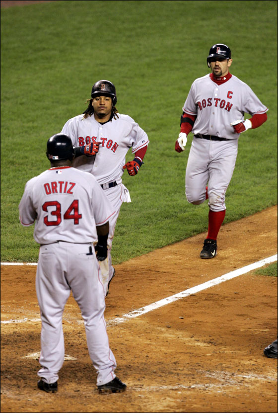 Boston Red Sox batter Jason Varitek (C) is welcomed at home plate by runners Manny Ramirez (L) and David Ortiz (R) after his three-run home run off New York Yankees relief pitcher Scott Proctor in the seventh inning of their American League game in New York's Yankee Stadium, June 8, 2006.