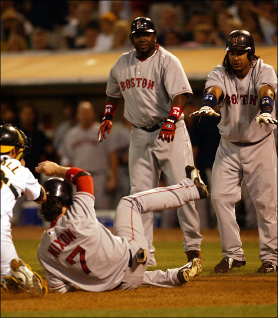 Red Sox David Ortiz, center, and Manny Ramirez, right, watch Trot Nixon slide safely past Oakland Athletic's catcher Jason Kendall, left, to score on a three-run hit by Jason Varitek in the eighth inning during a baseball game Tuesday, July 25, 2006 in Oakland, Calif. The Red Sox won 13-5.