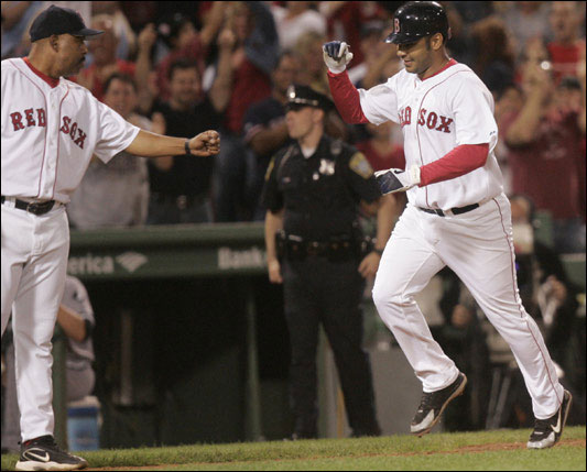 Red Sox infielder Carlos Pena rounds third base after hitting a game-winning home run during the 10th inning.  Red Sox third base coach Hale De Marlo offers congratulations. The Red Sox host the Chicago White Sox at Fenway Park in Boston, MA on Monday, September 4, 2006.