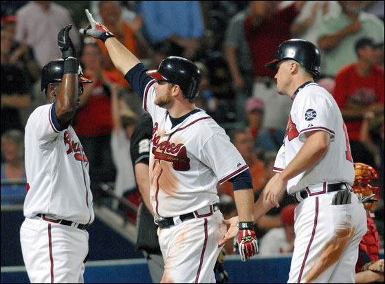 Atlanta Braves' Brian McCann, center, celebrates with Edgar Renteria, left, and Chipper Jones after McCann hit a three-run home run against the Boston Red Sox during the fifth inning of a Major League Baseball game Monday, June 18, 2007, at Turner Field in Atlanta.