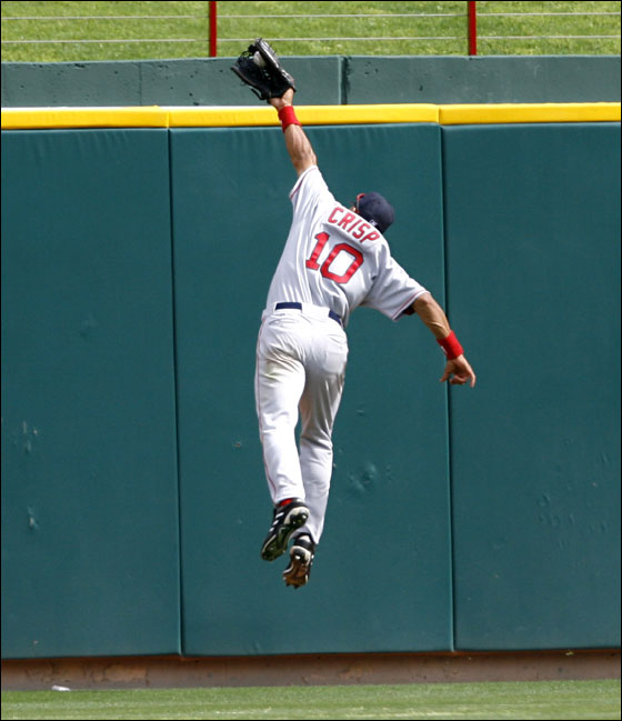 Coco Crips leaps over the wall to rob Texas Rangers Laynce Nix of an extra basses hit during 9th inning action on Monday  April 3, 2006