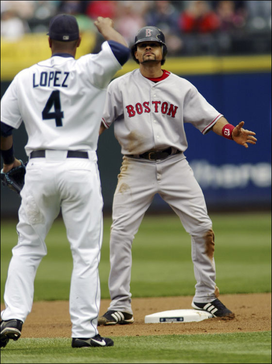 Red Sox baserunner Coco Crisp (R) reacts after getting caught stealing second base by Seattle Mariner second baseman Jose Lopez (4) during the first inning of their MLB American League baseball game at Safeco Field.