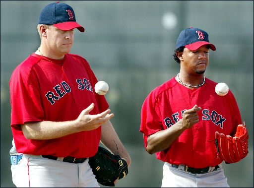 2.24.04: Red Sox pitcher Curt Schilling (left), has been in camp for some time, but today he was joined by fellow ace righthander Pedro Martinez (right) who worked out for the first time at the team's minor league facility. They are shown tossing baseballs, biding their time on the pitching mound, while listening to a coach go over some details before a morning drill.