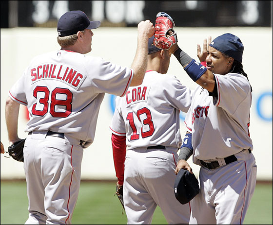 Boston Red Sox Curt Schilling is congratulated by Manny Ramirez after beating the Oakland Athletics in Oakland, California, June 7, 2007.