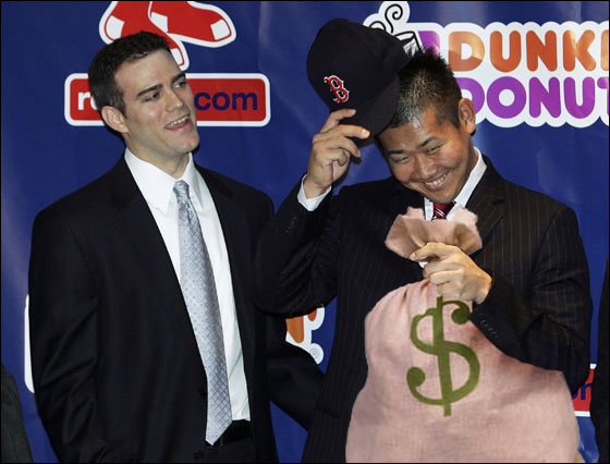 Daisuke Matsuzaka (R) hesitates before he tries on his hat as Red Sox general manager Theo Epstein looks on during a press conference announcing that the pitcher has signed with the Boston Red Sox on December 14, 2006 at Fenway Park in Boston, Massachusetts. Matsuzaka will earn $52 million over six years.
