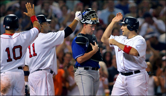 Red Sox catcher Doug Mirabelli makes his Kansas City counterpart John Buck a sad lookig backstop as he crosses the plate to high fives from Coco Crisp and Alex Gonzalez after his game tying seventh inning three run homer