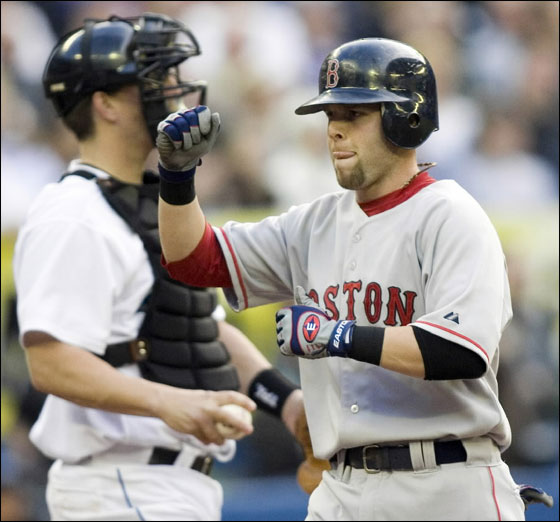 Dustin Pedroia pumps his fist as he crosses the plate in front of Toronto Blue Jays catcher Jason Phillips after hitting a three-run home run during second inning baseball action in Toronto on Tuesday, May 8, 2007