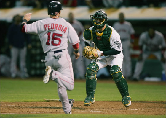 OAKLAND, CA - JUNE 04: Dustin Pedroia #15 of the Boston Red Sox waits to be tagged out at home by Jason Kendall #18 of the Oakland Athletics on a ball hit by David Ortiz in the ninth inning during a Major League Baseball game on June 4, 2007 at McAfee Coliseum in Oakland, California.