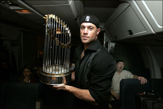 10.28.04: Sox Gabe Kapler holds the World championship trophy on a flight  from St. Louis where the Red Sox won the World Series. In the background Trot Nixon yawns.