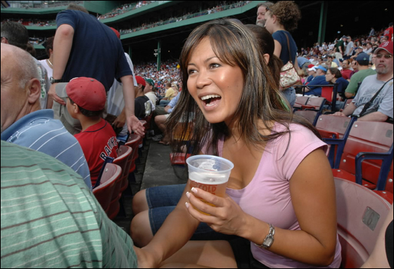 Hazel Mae, host of SportsDesk and Red Sox Rewind, both on NESN, talks shop with her neighbors in the bleachers at Fenway during the Monday, June 26, game against the Phillies.