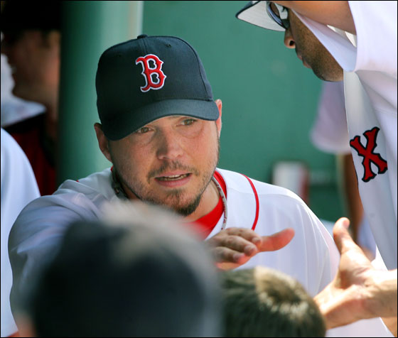 Red Sox pitcher Josh Beckett gets a hand in the dugout after he finished the eighth inning, his last on the afternoon, as he got the win in Boston's 1-0 victory over Kansas City at Fenway Park.