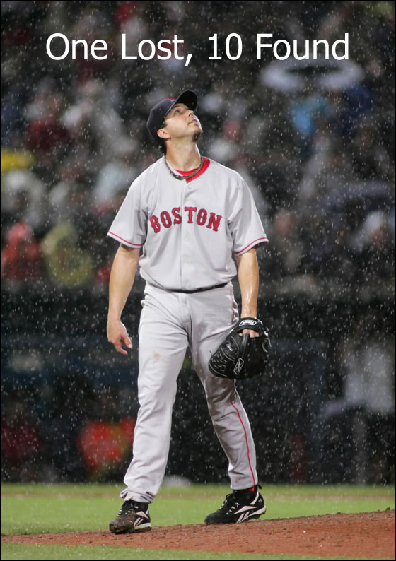 Boston Red Sox starting pitcher Josh Beckett looks up as the rain falls just before a rain delay in play against the Atlanta Braves during their MLB interleague baseball game in Atlanta, Georgia June 19, 2007