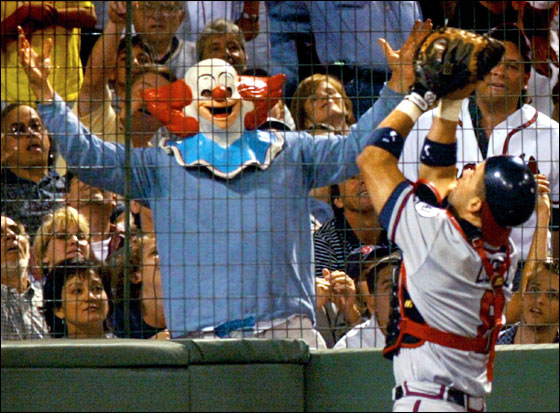 A fan dressed as a clown tries to distract Atlanta Braves catcher Javy Lopez (R) as Lopez catches a pop foul off the bat of the Boston Red Sox Dante Bichette in the seventh inning at Fenway Park in Boston, Massachusetts July 6, 2001.