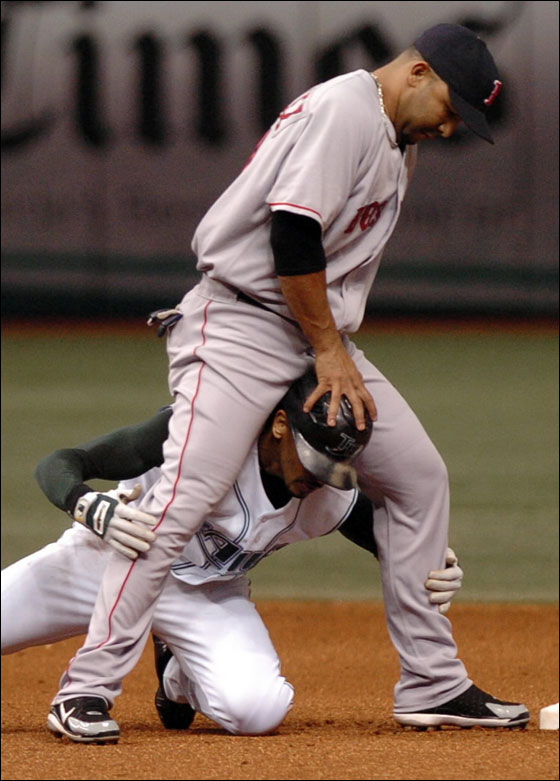 Red Sox shortstop Alex Gonzalez extricates Tampa Bay Devil Rays' Julio Lugo from his legs after forcing Lugo out at second base on a fielder's choice hit by Tampa Bay batter Carl Crawford during the fifth inning of a baseball game Tuesday, July 4, 2006, at Tropicana Field in St. Petersburg, Fla.