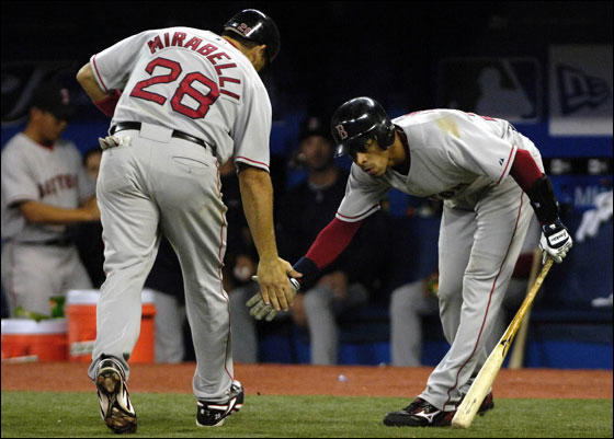 Boston Red Sox's Julio Lugo, right, celebrates with teammate Doug Mirabelli after scoring on his solo home run against the Toronto Blue Jays during sixth inning baseball action in Toronto, Wednesday, April 18, 2007.