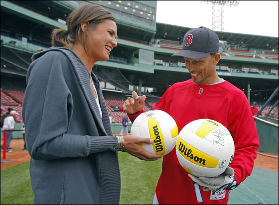 Professional volleyball player Logan Tom gets a couple of autographs on a pair of volleyballs from Red Sox shortstop Julio Lugo during batting practice at Fenway Park.