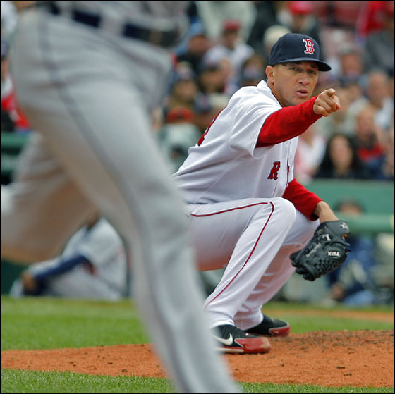 Red Sox starting pitcher Julian Tavarez points the way, as he throw to first to double up the Tigers Ivan Rodriguez (left) reaches its destination. The double play ended the top of the fourth inning.
