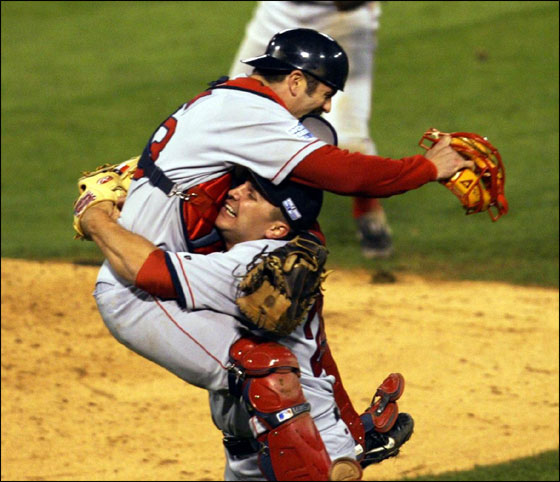 Red Sox's catcher Jason Varitek jumps into the arms of pitcher Keith Foulke after beating the St. Louis Cardinals 3-0 to win the World Series Wednesday, Oct. 27, 2004, in St. Louis. Celebrating in the background is teammate Bill Mueller.