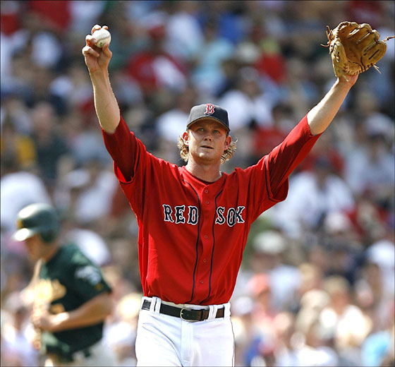 Red Sox pitcher Kyle Snyder stretches while walking towards first after walking Oakland Athletics' Marco Scutaro with the bases loaded to force in Bobby Crosby, rear, for the first run of a five run fifth inning in major league baseball at Fenway Park in Boston Sunday, July 16, 2006.