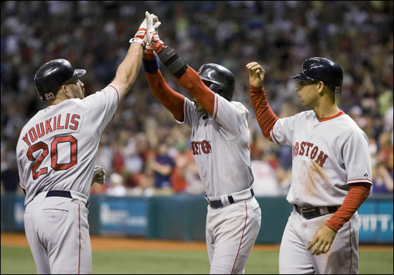Red Sox Kevin Youkilis is welcomed at home plate by the Red Sox Julio Lugo and Alex Cora after hitting a three-run home run against the Tampa Bay Devil Rays during the sixth inning of their American League baseball game in St. Petersburg, Florida July 27, 2007.
