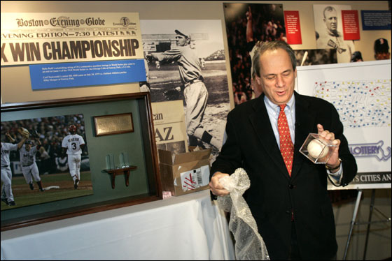 President/CEO of the Boston Red Sox Larry Lucchino unwraps the final out World Series ball at Fenway Park after it arrived by Brinks truck to the park.