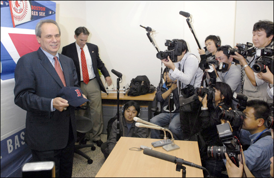 Red Sox President Larry Lucchino, left, holding the major league team's baseball cap is surrounded by Japanese photographers during a news conference in Tokyo Tuesday, Nov. 28, 2006, after meeting with representatives of Daisuke Matsuzaka's team, the Seibu Lions.