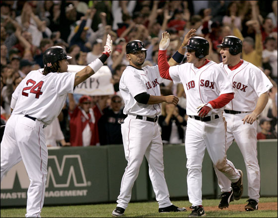 Manny Ramirez reaches out to congratulate  Kevin Youkilis, Alex Gonzalez and Mark Loretta in the 6th inning after they all scored on David Ortiz's double