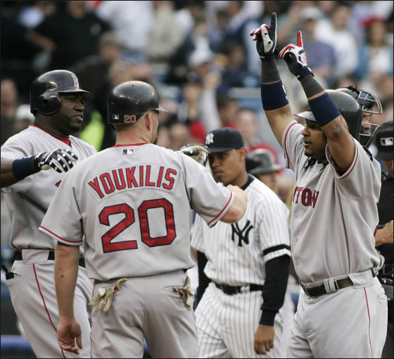 Red Sox batter Manny Ramirez is welcomed at the plate by runners David Ortiz and Kevin Youkilis after hitting a three-run home run off New York Yankees starting pitcher Mike Mussina in the first inning of their American League baseball game in New York May 22, 2007.