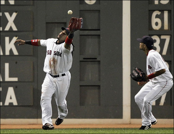 Red Sox centerfielder Coco Crisp, right, watches as left fielder Manny Ramirez plays a double off the wall by Kansas City Royals' Tony Pena, scoring Alex Gordon in the seventh inning of a baseball game Tuesday, July 17, 2007, in Boston.
