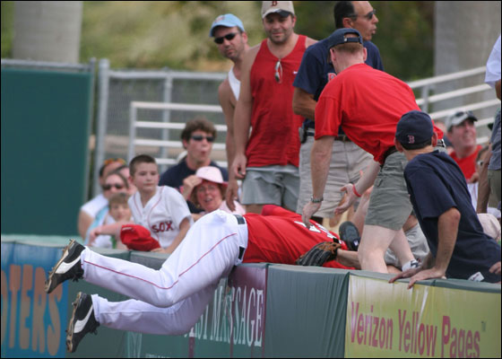 Trot Nixon of the Boston Red Sox falls into the stands as he makes the catch during the game against the Los Angeles Dodgers on March 13, 2006 at City of Palms Park in Fort Myers, Florida.