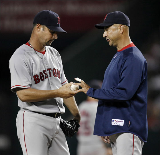 Boston Red Sox pitcher Tim Wakefield  hands over the ball to manager Terry Francona after giving up three runs to the Los Angeles Angels during the fifth inning of a MLB American League baseball game in Anaheim, California August 7, 2007.