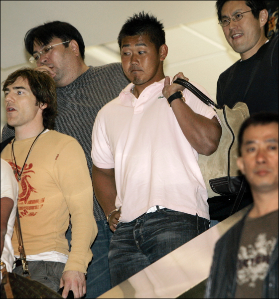 Boston Red Sox pitcher Daisuke Matsuzaka, in pink shirt holding bag over shoulder, arrives at Tampa International Airport, Monday, Feb. 12, 2007, in Tampa, Fla.