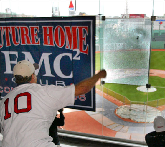 A pane of glass is shattered by a concrete baseball thrown by Dave Hixson from Hudson,on the tempered glass enclosure that  encloses the elevated Fenway Park .406 Club, as Red Sox President/CEO Larry Lucchino looks on. Hixson, an EMC employee was chosen for the honor, as he fired a pitch into the windshield-like glass, as it shattered. The glass will be coming down as the .406 Club will be converted into anew, open-air seating area called the EMC Club. The .406 Club is named after Red Sox legend, Ted Williams, and his batting average. The new EMC Club will be at the suite level, and will have exactly 406 seats.