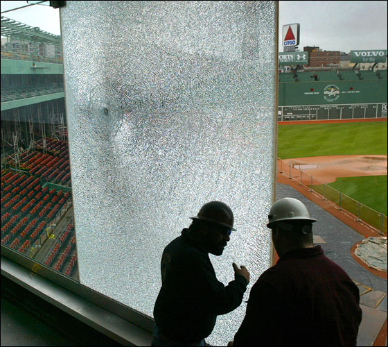 Construction workers Costa Georgoudis and Jason Van Czak survey the two panes of glass shattered by a concrete baseball thrown by Dave Hixson from Hudson,on the tempered glass enclosure that  encloses the elevated Fenway Park .406 Club.