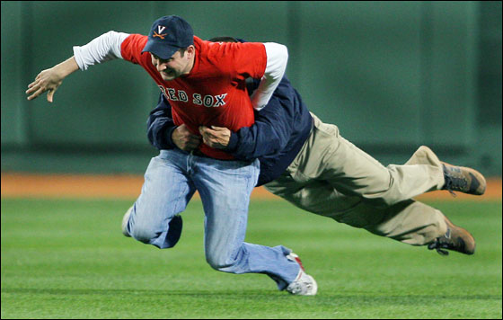 A Fenway Park security official makes a great open field tackle, as he brings down a fan who ran into the outfield during the ninth inning of Boston's 9-1 victory over Tampa Bay. The man was escorted off the field and lead away to jail no doubt.