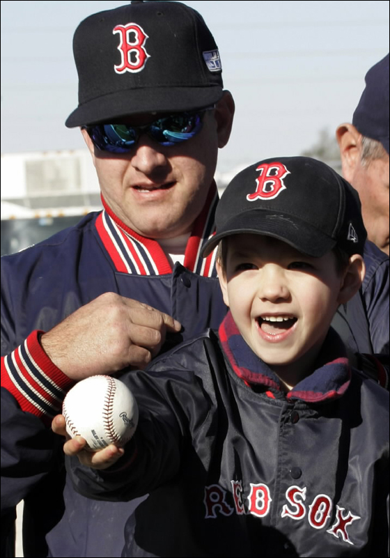 Boston Red Sox fan Robert Gravel of Ocala, Fla., left, and his son Robbie, 5,right, wait to get autographs from players at baseball spring training camp in Fort Myers, Fla, Monday, Feb. 19, 2007.