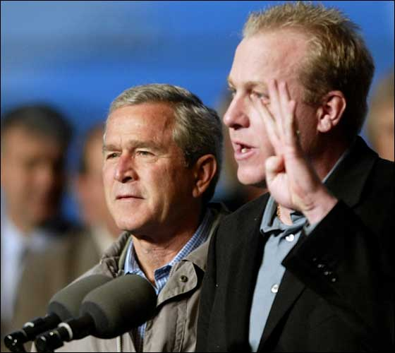 11.1.04: US President George W. Bush (left) listens to World Series Championship Boston Red Sox pitcher Curt Schilling as he introduces him to the crowd during a campaign rally at ABX Air Hangar 01 November 2004