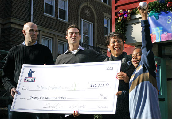 Paul Epstein, left, his brother Theo, middle left, and Joan Wallace-Benjamin, President and CEO of The Home for Little Wanderers, middle right, all react to Nicholas Davis, of Brockton, Mass., while he holds a baseball given to him from Theo high in the air during a press conference to kick off a gift drive for The Home for Little Wanderers in Boston on Thursday.