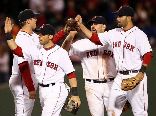 Jonathan Papelbon, Marco Scutaro, Kevin Youkilis and Mike Lowell congratulate each other after they defeated the Baltimore Orioles 7-6 in a baseball game at Fenway Park in Boston, Saturday, April 24, 2010.