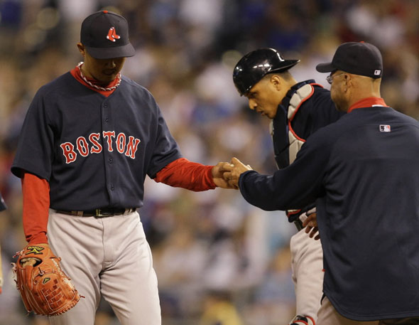 Hideki Okajima, left, is taken out of the game by manager Terry Francona, right, during the eighth inning of a major league baseball game against the Kansas City Royals Friday, April 9, 2010, in Kansas City, Mo.