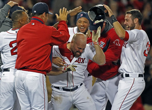 Kevin Youkilis is mobbed by teammates following his 12th inning game winning hit that gave Boston an 8-7 victory over Texas. The Boston  Red  Sox take on the Texas Rangers at Fenway Park