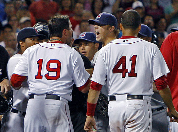 Josh Beckett and  Indians pitcher Jensen Lewis scream at each other at center right restrained after a tight 8th inning pitch.The Boston Red Sox take on the Cleveland Indians at Fenway Park.