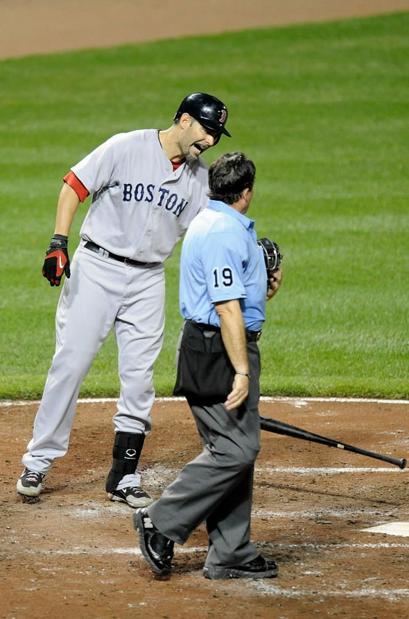 Mike Lowell #25 of the Boston  Red  Sox  argues with home plate umpire Ed Rapuano after being called out on strikes against the Baltimore Orioles at Camden Yards on August 31, 2010 in Baltimore, Maryland.