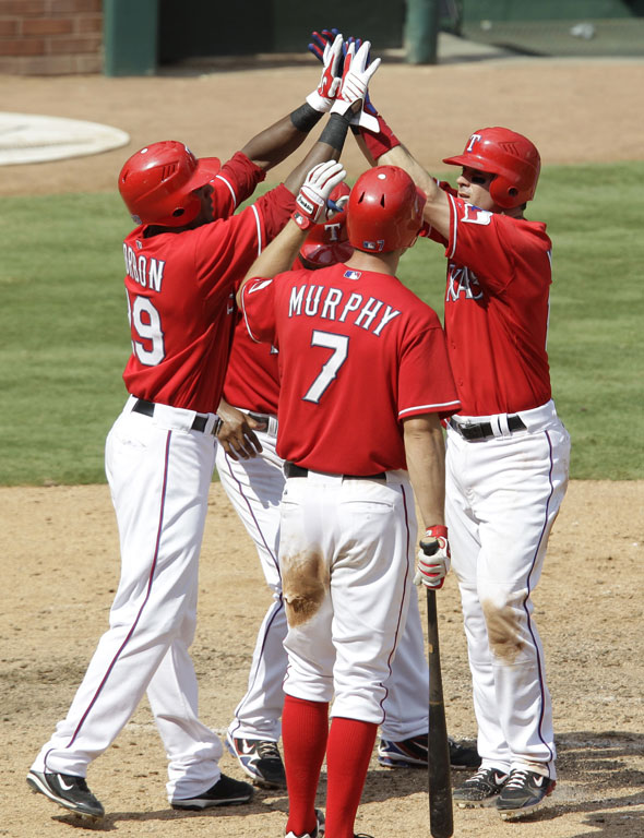 David Murphy, Julio Borbon, left, and Elvis Andrus, rear, congratulate Michael Young, right, on his three-run home run off of  Manny DelTimlin in the seventh inning of a baseball game Sunday, Aug. 15, 2010, in Arlington, Texas. The Rangers won 7-3.