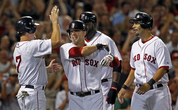 Ryan Kalish (second from left)) is greeted at the plate by teammates J.D. Drew, David Ortiz and Mike Lowell following his fourth inning grand slam. The Boston Red Sox take on the Los Angeles Angels of Anaheim at Fenway Park.