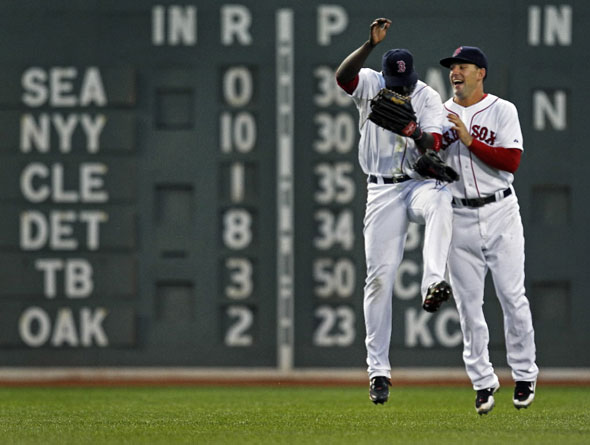 Bill Hall (left) and Ryan Kalish (right) leap in celebration following Boston's 5-0 victory, but they gained no ground in the standings, as both the Yankees and Tampa Bay won earlier (scores at left).