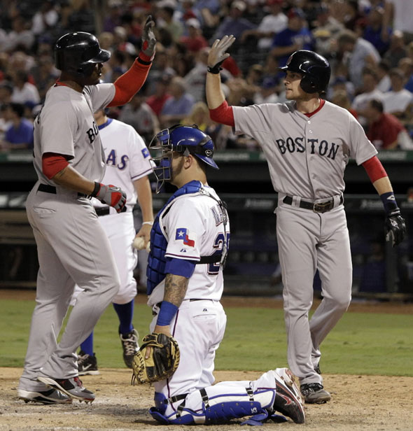 Texas Rangers catcher Napoli kneels by home plate as Boston Red Sox's Crawford, left, and Lowrie, right, celebrate Crawford's two-run home run that also scored Lowrie in the seventh inning of a baseball game on Wednesday, Aug. 24, 2011, in Arlington, Texas.