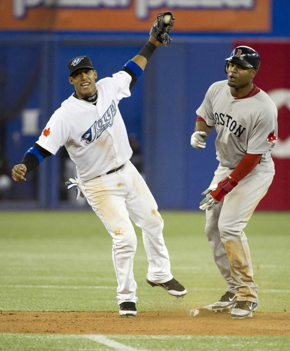 Toronto Blue Jays Yunel Escobar celebrates tagging out Boston Red Sox Carl Crawford on steal attempt during the seventh inning of their American League MLB baseball game in Toronto, May 11, 2011.