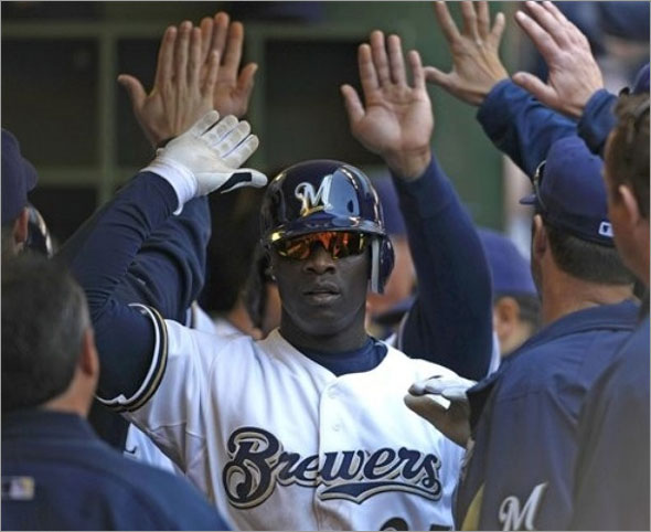 Milwaukee Brewers' Mike Cameron high fives teammates after his two-run home run against the Cincinnati Reds during the third inning of a baseball game Sunday, May 31, 2009, in Milwaukee