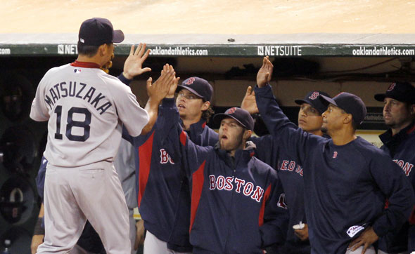 Daisuke Matsuzaka is congratulated by his team-mates after being relieved in the seventh inning of their MLB American League baseball game against the Oakland Athletics in Oakland, California July 19, 2010.